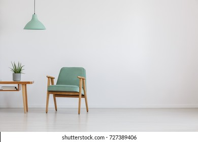 Soft mint green chair in retro style in open space with mint lamp and plant on wooden table