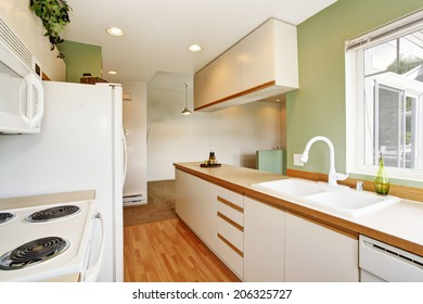 Soft mint kitchen interior with white cabinets and appliances
