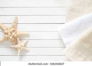 Soft modern bathroom decor for advertising, cover. Light towels, starfish on white wooden background. Flat lay, top view, copy space