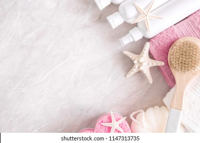 Soft modern bathroom decor for advertising, covers. Pink towels, cosmetic bottles, bath accessories, starfish on a light marble background table. Flat lay, top view, copy space