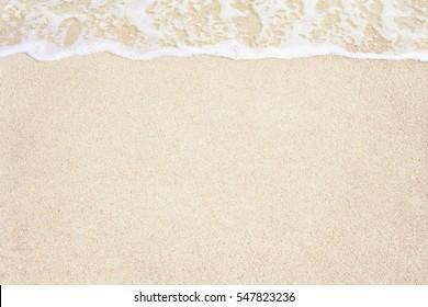 Soft ocean wave on sandy beach background.