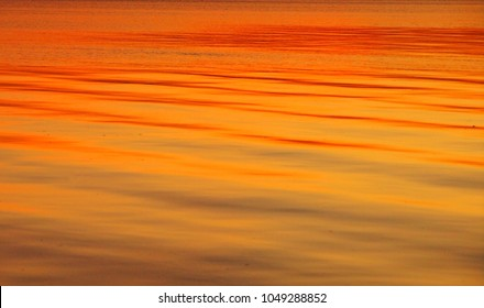Soft ocean waves at sunset glow orange, Thailand