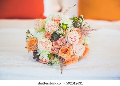 Soft orange and pink bridal bouquet on bed