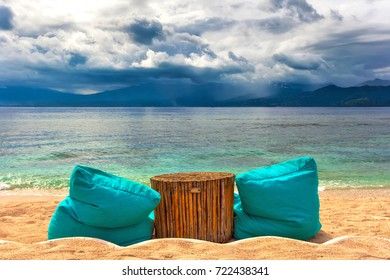 Soft ottomans around a wooden bamboo table on a sunny beach against the background of the Bali Sea and the approaching rain clouds on the shore of another island. Gili Trawangan, Indonesia.