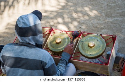 Soft and partial focus image the back view of man who is playing Bonang, the Javanese traditional music instruments.