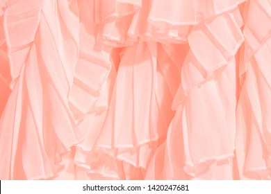 Soft pastel color chiffon fabric folds. Coral dress with ruffles and frills. Trendy color of the year.