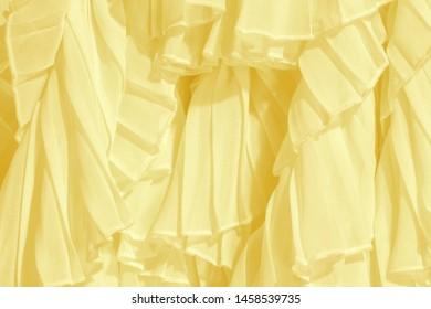 Soft pastel color chiffon fabric folds. Yellow dress with ruffles and frills.
