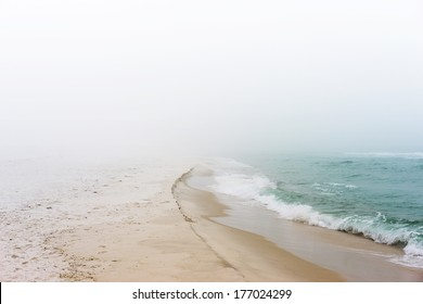 Soft pastel landscape photo of waves breaking on a pristine, peaceful, unpopulated beach.