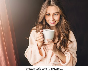 Soft photo of fresh young woman in pink tender bathrobe drink tea and smiling. Pretty girl with perfect  wavy hairs enjoying  early  sunny morning.
