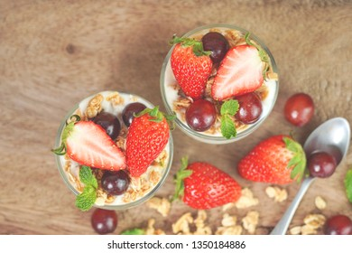 Soft photo of homemade granola with yogurt and fresh strawberries , grapes in glass cup on wooden background. Top view.