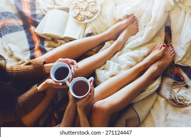 Soft photo of two  sisters  on the bed with old books and cup of tea in hands wearing cozy sweater , top view point. Two best friends enjoying morning.