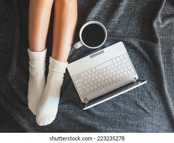 Soft photo of woman on the bed with notebook and cup of coffee, top view point