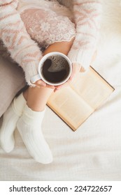 Soft photo of woman on the bed with old book and cup of coffee in hands, top view point. Cozy, comfy, soft