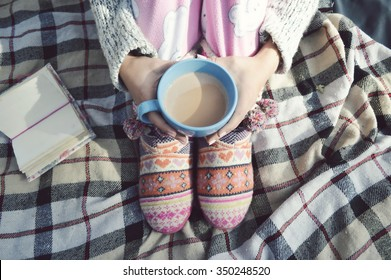 Soft photo of woman on the bed with notebook,  cup of coffee, top view point.Female legs in warm woolen socks