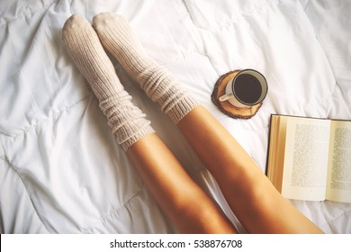 Soft photo of woman on the bed with book and cup of coffee, top view