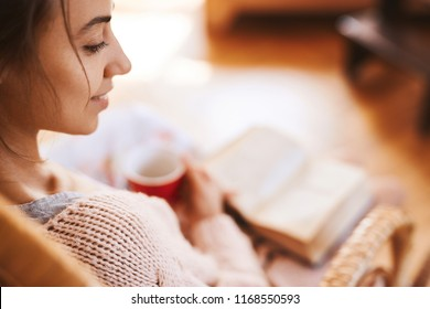 Soft photo of woman in a wicker chair with old book and cup of coffee. Woman wearing in cozy knitted pink sweater, selective focus, focus on the eye