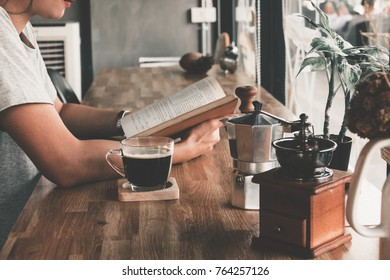 Soft photo of young girl reading a book and drinking coffee