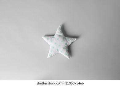 Soft pillow in shape of star on light background