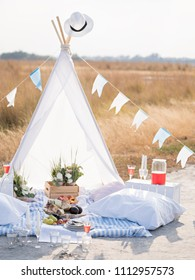 Soft pillows and tasty food for romantic picnic lying near cloth tent in beautiful nature.