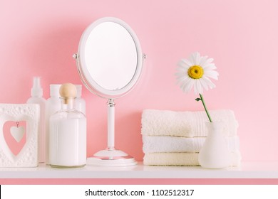 Soft pink light bathroom decor for advertising, design, cover, set of cosmetic bottles. Beautiful flowers in a vase on a pink wall background, mirror on a wooden shelf. mock up