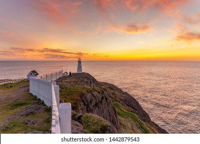 Soft pink and orange clouds light up the sky before sunrise over a white lighthouse sitting at the edge of a rocky cliff. Cape Spear National Historic Site, St Johns Newfoundland.