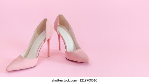 Soft pink suede high heels on matching background