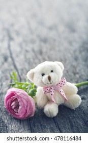 Soft plush teddy bear with a pink ranunculus flower on wooden vintage background for an anniversary or Valentines celebration