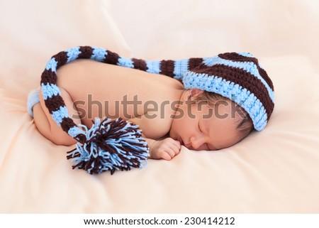677809164ba Soft portrait of newborn baby boy kid on beige fabric background in striped  knitted cap hat