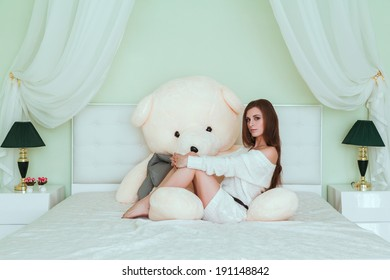 Soft portrait of young woman sitting on the bed at home