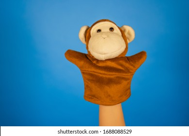 Soft puppet toy on hand on blue background. Concept of puppet show. Close-up of hand with puppet monkey.