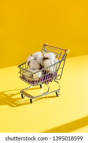 Soft raw cotton balls sitting in a tiny small shopping cart with dramatic shadows. Cotton represents the fashion clothing industry. Shot on yellow background.