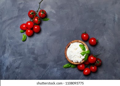 Soft ricotta cheese in a wooden bowl with green basil and cherry tomatoes, gray stone background, top view