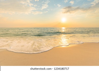 Soft sea waves and bubbles on the beach with sunset sky background.