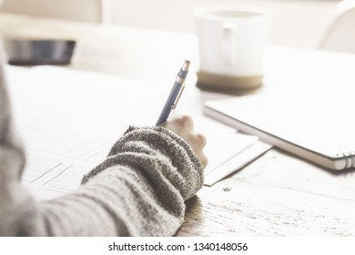 Soft and selective focus the arms of a woman wearing a gray sweater Pen handle is writing a book.