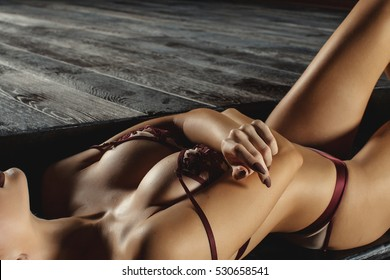 Soft shadows on the body. Beautiful boobs. Tanned blonde. Boudoir advertising. Girl lies on the floor. Sexy figure