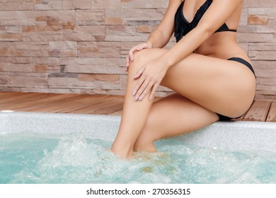 Soft skin. Cropped view of a young lady scrubbing her skin on legs near the Jacuzzi