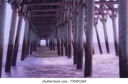 Soft slow water movement of waves crashing under the pier. Garden City Beach, South Carolina