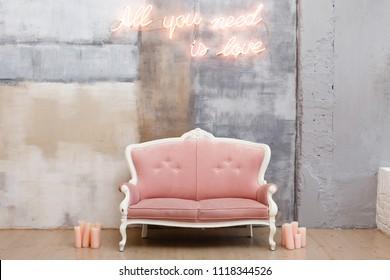 ネオンの文字が書かれた漆喰の壁の近くにある柔らかいソファ「愛しさしか必要ない」。 布張りの肘掛け椅子