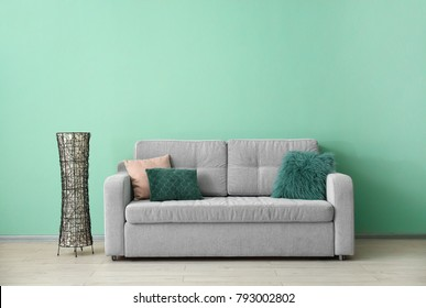 Soft sofa with pillows near color wall