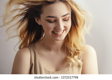 soft studio portrait of a beautiful sincerely laughing girl, young woman face with curly hair disheveled from wind , the concept of natural beauty, body care, cosmetics