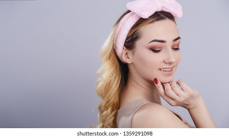 soft studio portrait of a beautiful young woman with fluffy soft hoop on head that picks hair, fresh girl face with make up, the concept of natural beauty, body care, cosmetics