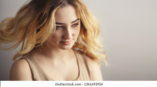 soft studio portrait of a beautiful young woman, girl face with curly hair disheveled from wind , the concept of natural beauty, body care, cosmetics