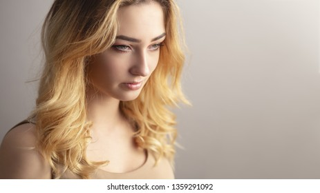 soft studio portrait of a confident young woman, girl face with curly hair disheveled from wind , the concept of natural beauty, body care, cosmetics