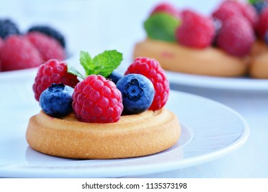 Soft sugar cookies topped with fresh forest fruits, raspberries, blackberries, blueberries on white plate