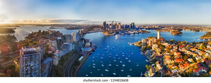 Soft sunlight in the morning over Sydney city CBD landmarks around Harbour and Lavender bay from Lower North SHore along Sydney Harbour bridge and The Rocks with Barangaroo.
