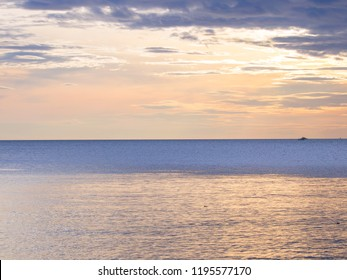 A soft sunset of blended yellows on a calm ocean in east Thailand