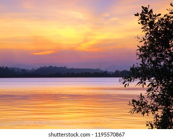 A soft sunset of blended yellows and purples on a calm ocean in east Thailand