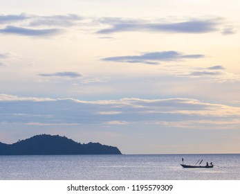 A soft sunset with wispy clouds on a calm ocean with a small island and fishing boat in east Thailand