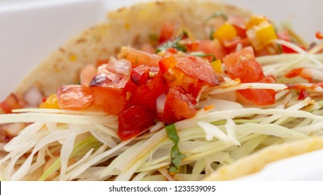 A soft taco shell with cabbage slaw and colourful red and orange pico de gallo using tomatoes and bell peppers. Taco came from a food truck.