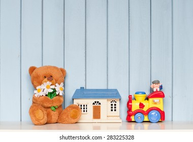 soft teddy bear with flowers, toy house and mechanical locomotive on the bookshelf on blue wooden background in the children's room
